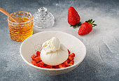 Gourmet burrata cheese with  strawberry tartare and honey in a light plate on a gray concrete or stone background. Breakfast. Delicious appetizer. Mediterranean (Italian) cuisine. Selective focus, copy space