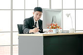 businessman or accountant hand holding pen working making notes and using computer