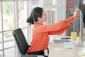 Businesswoman in office working hard. She is sticking paper reminders on computer monitor