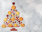 Culinary background of sugar cookies, almonds and spices in the form of a Christmas tree. Delicious biscuits, cinnamon cardamom, cloves, star anise, fresh berries cranberries and caramel on a grey concrete surface . Copy space