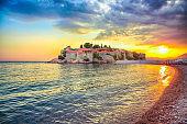 Fantastic sunset view of luxury beach and islet Sveti Stefan near Budva