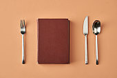 Book, fork, knife and spoon served isolated on beige background, conceptual photography for food blog or advertising