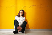 Young pretty girl student in white hoodie sitting on the floor and smiling in the sunlight against yellow wall.
