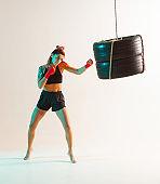 Sporty female in stylish sportswear training with tyres in studio in neon light. Women's sport poster
