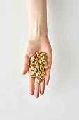 100 calories of healthy snack of pistachios in hand isolated on a white background, healthy food and lifestyle