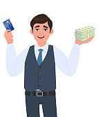 Young businessman showing credit card and cash, money, currency notes in hand. Successful person in vest suit holding debit, ATM card. Stylish male character design illustration in vector cartoon.