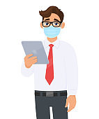 Young business man in safety medical mask, holding tablet computer device. Person using digital touch pad. Modern technology lifestyle. Corona virus epidemic outbreak. Cartoon illustration in vector.