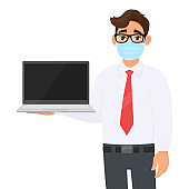 Young businessman in safety medical mask showing laptop computer screen. Person holding latest PC. Male character in formal wear with eyeglasses. Corona virus epidemic outbreak. Cartoon illustration