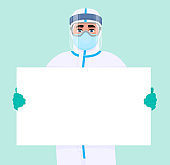 Male doctor in safety protection suit, mask, glasses and face shield showing blank poster, banner. Physician or surgeon holding empty white board. Person wearing personal protective equipment uniform.