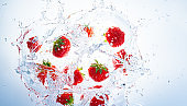 Strawberries splashing into clear water, view from top