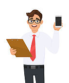 Young businessman in eye glasses holding clipboard and showing mobile, cellphone or smartphone screen. Person carrying document, file, checklist. Male character keeping folder. Cartoon in vector.