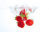 Strawberries falling into water causing bubbles all around it. Healthy food concept