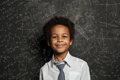 Happy smart black child student on blackboard background with science and maths formulas