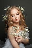 Cute young woman with long blonde curly hairdo and flowers