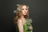 Young perfect woman with long healthy curly hair and flowers on black background
