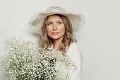 Perfect woman wearing summer season hat holding flowers on white background
