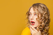 Surprised woman with blonde curly hair on yellow background