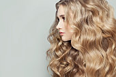Beautiful woman with long healthy blonde curly hair, female face profile closeup