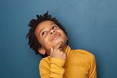 Little black child boy thinking on blue background