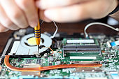 Expert is repairing to inner of laptop with screwdriver. The design restrictions on power, size, and cooling of laptops limit the maximum performance of laptop parts compared.