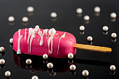 Pink Chocolate Popsicle on Dark Reflective Background. Creative Party Food