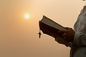 A young woman hugged the Bible and held a cross. Considered as a sacred blessing of God Spirituality and worship and praise of Christians And religious beliefs. Asking for a blessing.