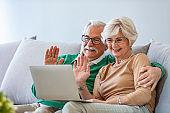 Happy senior couple having video call on laptop.