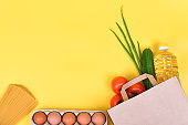 Paper bag with food supplies for the period of quarantine isolation on a yellow background. Copyspace.