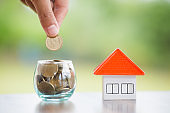 An orange roof house near a coin in a glass bottle.The investor's hand is about to drop a coin into a glass bottle.Saving money, buying a home and Real estate mortgages and investment for home trading