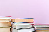 Stacks of books several on a pink background close-up. Back to school, education, learning,