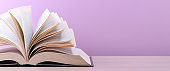 The book is open, lying on the table, sheets fanned out on a pink background.