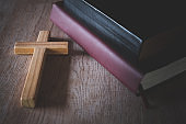 The Bible and the cross are placed near each other. The concept of asking for blessings from God. The power of holiness which brings luck and shows forgiveness with the power of religion.