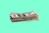 A bundle of one hundred dollar bills on a green background. Isolated