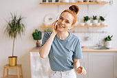 Portrait of happy carefree redhead young woman listening music in wireless headphones while sitting at the desk
