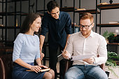 Three colleagues of man and woman gather for meeting at office room