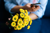 Close-up of hands of unrecognizable woman holding bouquet yellow chrysanthemums and using cell phone