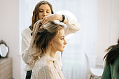 Two make-up artistes applies hair and makeup to the bride in dressing room.