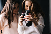 Women model and female photographer watching photos in studio.
