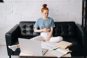 Dissatisfied redhead young businesswoman sitting at the desk with laptop computer and paper documents