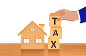Vector of a house and a business man composing the word tax from wooden cubes