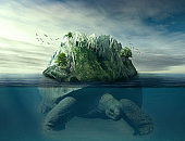 Giant turtle carrying island on the back swimming under the ocean surface in blue water.
