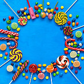 Colored candies, lollipops and marmalade on a blue background round frame. Top view, flat lay.