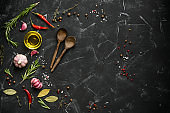 Black stone culinary background with seasonings, spices, vegetables, oil. Top view, flat lay, copy space.