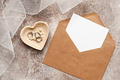 Wedding invitation template. Blank paper mockup card in envelope, tulle ribbon and heart bowl with jewelry. Women's minimal composition. Beige grunge background. Top view, flat lay.