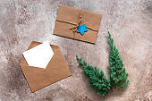 Beautiful Christmas composition. Blank card in an envelope, juniper branches and vintage letter. Beige textured grunge background. Mockup of invitation or greeting card. Top view, flat lay.
