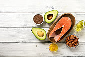 Fresh products rich in omega-3 fatty acids on a white wooden background. Healthy eating concept. Salmon, avocado, flax seeds, fish fat capsules, oil, almonds. Top view, flat lay.