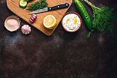 Traditional greek tzatziki sauce with ingredients on dark rustic background. Greek yogurt with cucumber, dill, garlic and lemon. Top view, copy space, flat lay.