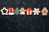Christmas various colored gingerbread cookies in a row on a black stone background, border. Top view, flat lay