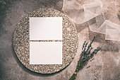 Blank paper cards on a granite plate, dry lavender bouquet and ribbon. Wedding invitation mockup. Stylish design template. Beige grunge background. Top view, flat lay.