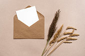 Blank white paper in a brown craft envelope and dry autumn grass. Brown paper background. Mock-up of invitation and greeting card. Modern minimalism style. Top view, flat lay.